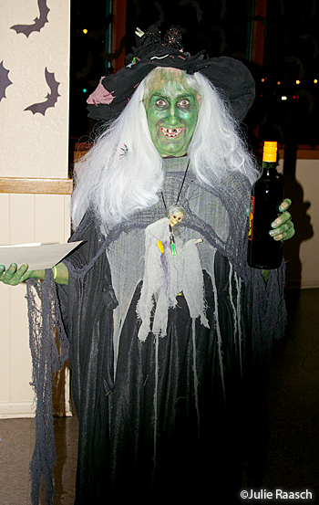 witch with green face, white hair and black/grey clothing
